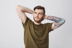 英俊的有胡子的白种人人画象有纹身花刺的在握在头后的胳膊和时髦的发型手,看 库存照片