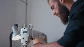 英俊的有胡子的裁缝人在自己的工作室缝合流行的服装 影视素材