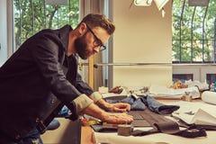 英俊的有胡子的裁缝做测量牛仔裤布料样品在缝合的车间 图库摄影
