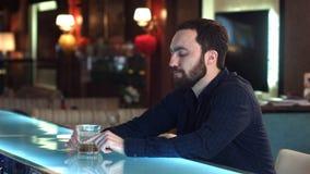 英俊的沉思人在客栈时看起来向前并且认为,当坐在酒吧柜台 免版税库存图片