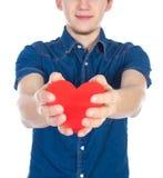 英俊的浅黑肤色的男人供以人员拿着红色心脏,隔绝在白色背景 免版税库存照片