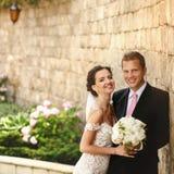 英俊的浪漫摆在新郎和美丽的深色的新娘近 库存图片