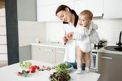 英俊的深色头发的母亲烹调沙拉早餐和谈话在电话,当站立在桌上的小逗人喜爱的儿子近时 免版税库存照片