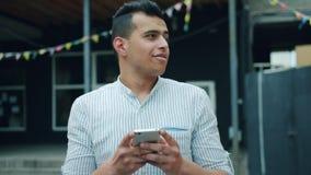 英俊的混合的族种人画象使用智能手机触摸屏的外面 股票视频