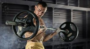 英俊的爱好健美者人特写镜头照片在手准备做与杠铃的锻炼在健身房,保留杠铃板材 库存照片
