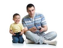英俊的父亲和他逗人喜爱的矮小的被隔绝的儿子演奏比赛控制台的和微笑 免版税库存图片