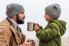 英俊的父亲和儿子有热的饮料的在金属 免版税库存照片