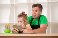 英俊的父亲和逗人喜爱一点女儿烹调 免版税库存图片