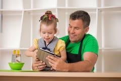 英俊的父亲和逗人喜爱一点女儿烹调 免版税库存照片