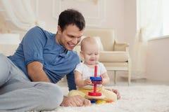 年轻英俊的父亲和逗人喜爱的儿子在儿童居室演奏大厦成套工具坐一张地毯 免版税库存图片