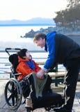 英俊的父亲谈话与残疾两种人种的儿子户外 免版税库存图片