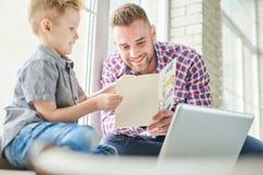 英俊的爸爸读书父亲节卡片 免版税库存图片