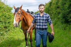英俊的牛仔,在马鞍,马背adn起动的马车手 库存图片