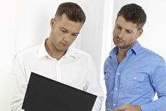 英俊的生意人与膝上型计算机一起使用 免版税库存图片