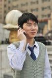 英俊的生意人他的移动电话 库存图片
