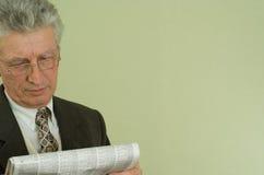 英俊的生意人读了报纸 图库摄影