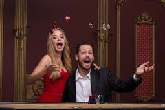 英俊的男人和美丽的妇女在赌博娱乐场 图库摄影