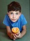 英俊的男孩吃桔子接近的画象 库存照片