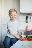 英俊的男孩在厨房里在家烹调 健康的食物 库存图片