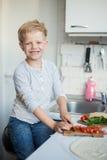 英俊的男孩在厨房里在家烹调 健康的食物 免版税库存图片