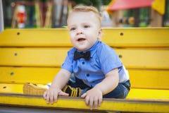 英俊的男孩坐长凳 免版税库存照片