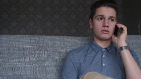 英俊的男孩少年谈话在电话坐一个灰色沙发 免版税库存图片