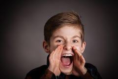 英俊的男孩尖叫对照相机反对灰色 免版税库存照片