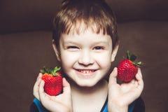 英俊的男孩拿着一个草莓 免版税库存照片