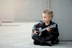 英俊的男孩画象皮夹克和易洛魁族的理发的与吉他 库存照片