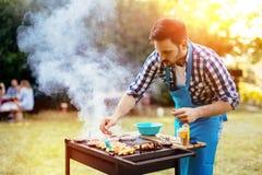 英俊的男性准备的烤肉 免版税库存照片
