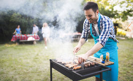 英俊的男性准备的烤肉 免版税库存图片