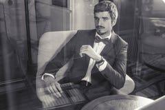 英俊的男性吃法国早餐在室内咖啡馆 库存照片
