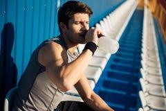 年轻英俊的男性在锻炼以后的运动员饮用水 免版税库存照片