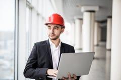 英俊的男性工程师为工作使用一个笔记本 免版税库存照片