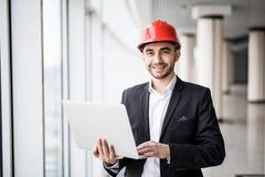 英俊的男性工程师为工作使用一个笔记本 免版税库存图片