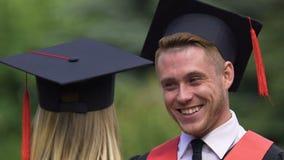 英俊的男性毕业生挥动与小姐,庆祝生活的滑稽的学生 影视素材
