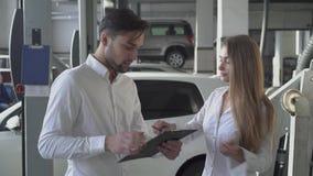 英俊的男性经理告诉俏丽的客户如何填好机器修理合同并且采取在汽车服务的钥匙 影视素材