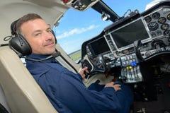 英俊的男性飞行员在驾驶舱内 免版税库存照片