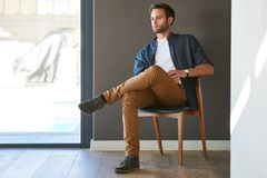 英俊的白种人人在家坐现代木椅子 库存图片