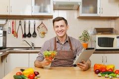 英俊的白种人年轻人,坐在桌上 健康生活方式 烹调可口家庭自创食谱的砂锅 食物准备 库存照片