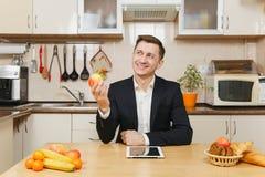 英俊的白种人年轻人,坐在桌上 健康生活方式 烹调可口家庭自创食谱的砂锅 食物准备 免版税库存照片