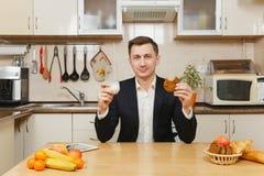 英俊的白种人年轻人,坐在桌上 健康生活方式 烹调可口家庭自创食谱的砂锅 食物准备 免版税库存图片