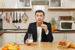 英俊的白种人年轻人,坐在桌上 健康生活方式 烹调可口家庭自创食谱的砂锅 食物准备 免版税图库摄影