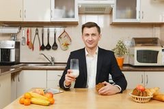 英俊的白种人年轻人,坐在桌上 健康生活方式 烹调可口家庭自创食谱的砂锅 食物准备 库存图片