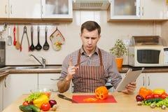 英俊的白种人年轻人,坐在桌上 健康生活方式 烹调可口家庭自创食谱的砂锅 食物准备 图库摄影