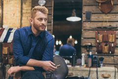 英俊的白种人男性理发师画象有时兴的发型的 库存照片