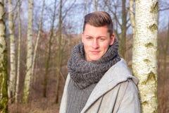 英俊的白肤金发的人在寒冷的森林里 库存图片