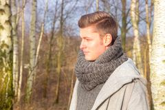 英俊的白肤金发的人在寒冷的森林里 库存照片
