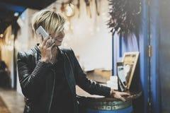 英俊的白肤金发的妇女握智能手机手和谈话与朋友 被弄脏的背景 水平 Bokeh和 库存图片