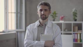 英俊的看在照相机藏品片剂的白色长袍的技巧微笑的人画象  现代的成人医生 股票视频